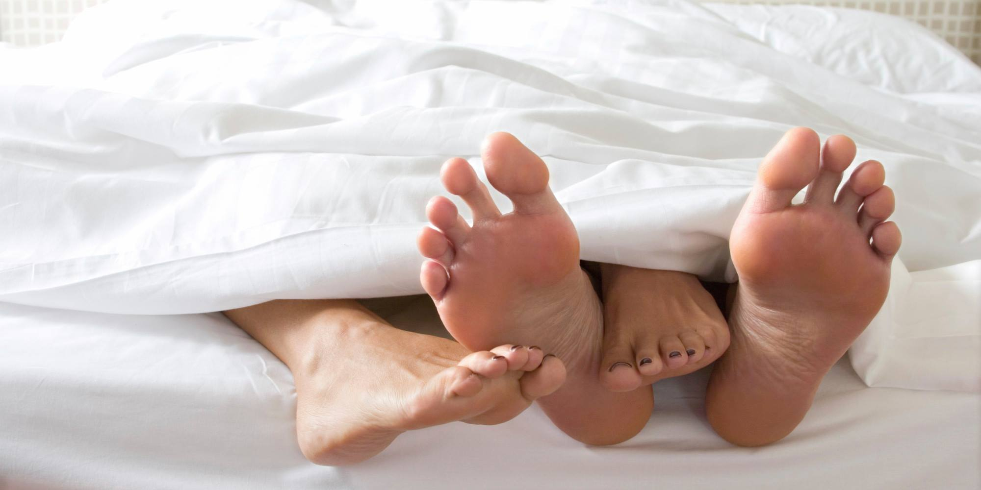 A couple in bed, with just their feet showing and white sheets