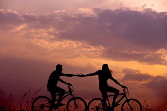 two people cycling with a sunset in the background